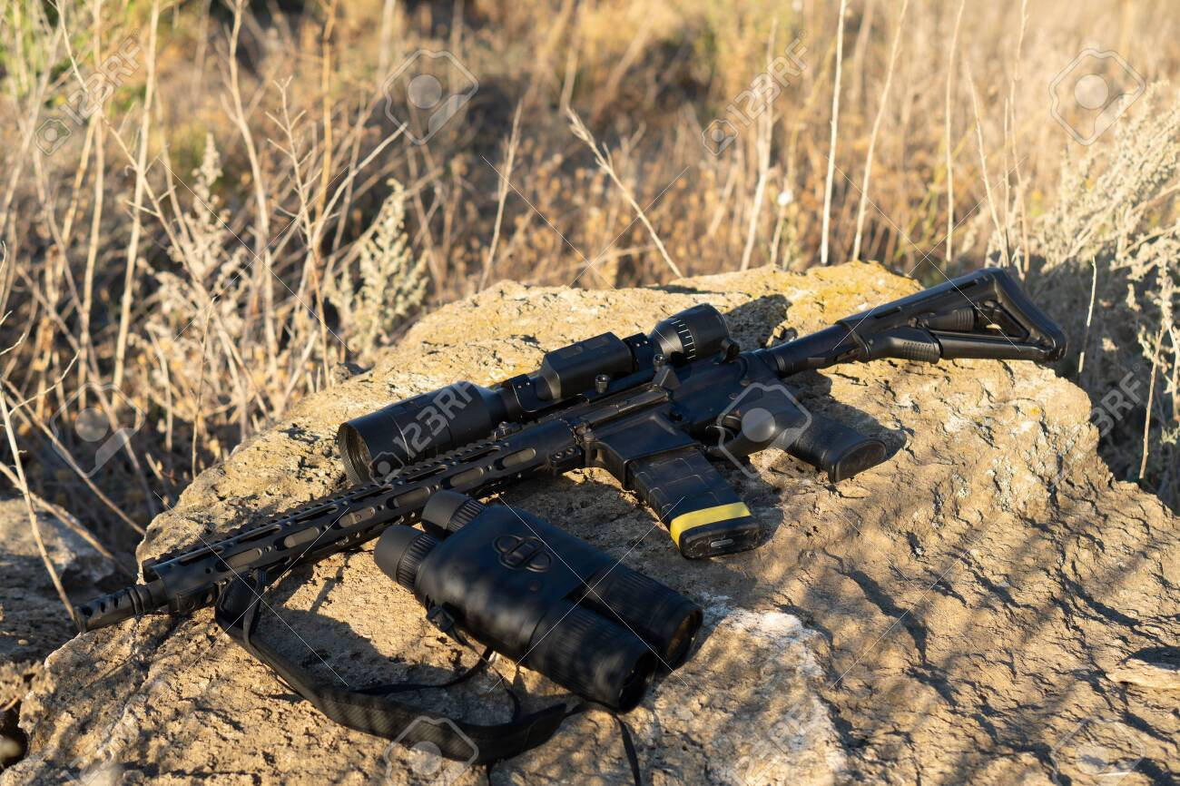 A rifle with a telescopic sight and binoculars on a stone background. Hunting and observation technologies - 155796838