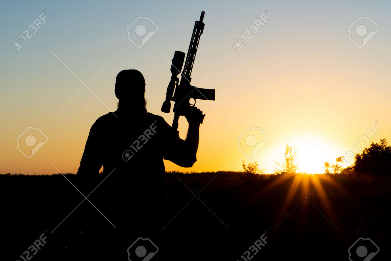 Silhouette of a man with a weapon in his hands on a sunset background - 155796847