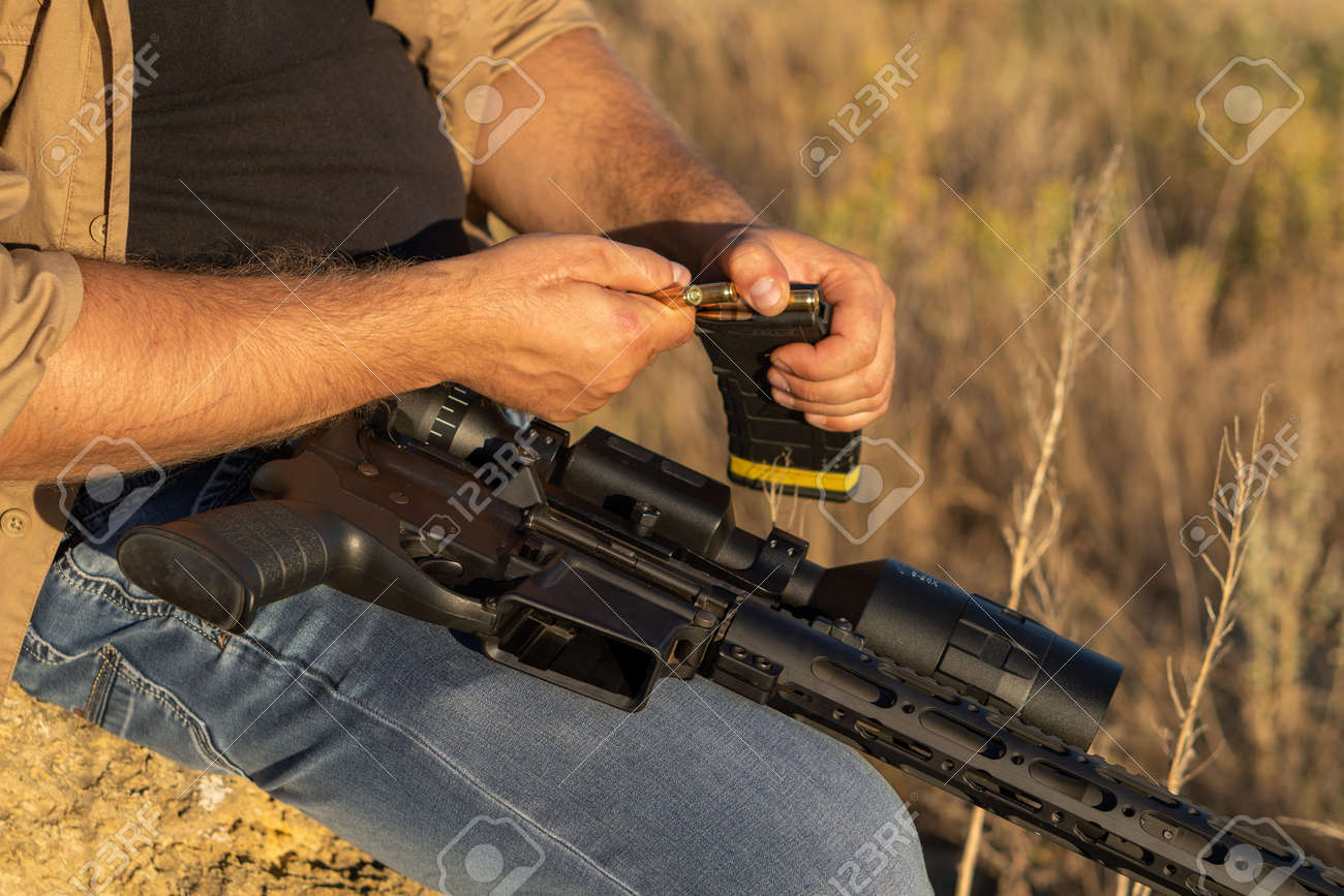 A rifle in a mans hand, close-up. Hunter with a weapon on the hunt against the background of a beautiful summer landscape - 155640479