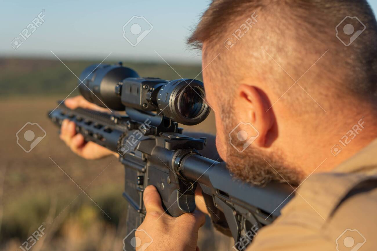 A hunter with a weapon on the hunt against the backdrop of a beautiful summer landscape. Shooter sighting in the target. The Bearded man is on the hunt. Soft focus - 155640480