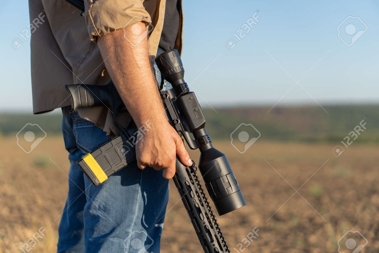 A rifle in a mans hand, close-up. Hunter with a weapon on the hunt against the background of a beautiful summer landscape - 155623098