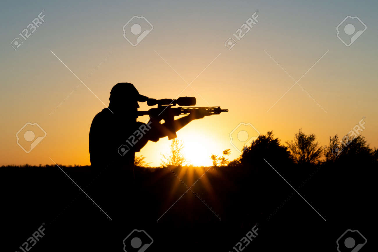 Silhouette of a man with a weapon in his hands on a sunset background - 155623103