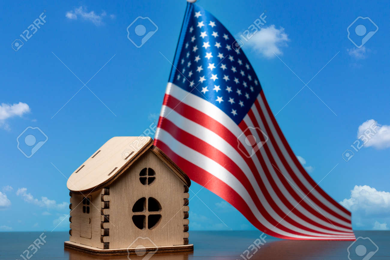Small wooden house and USA flag, sky on background. Real estate concept, copy space - 163114076
