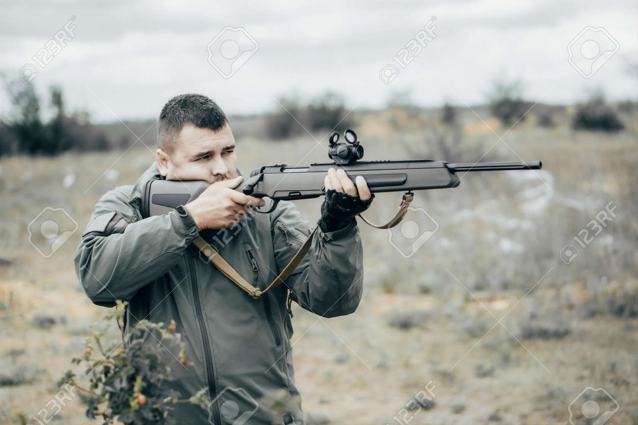 Man shoots a rifle. Private military contractor or hunter - 164160325
