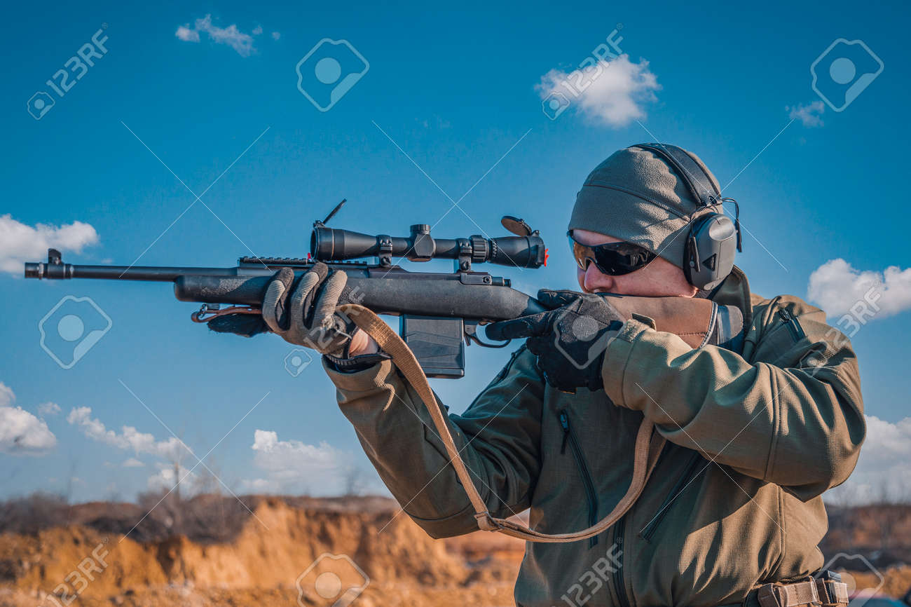 Portrait of a shooter with a rifle. European shoots a rifle with a optics sight - 164815590