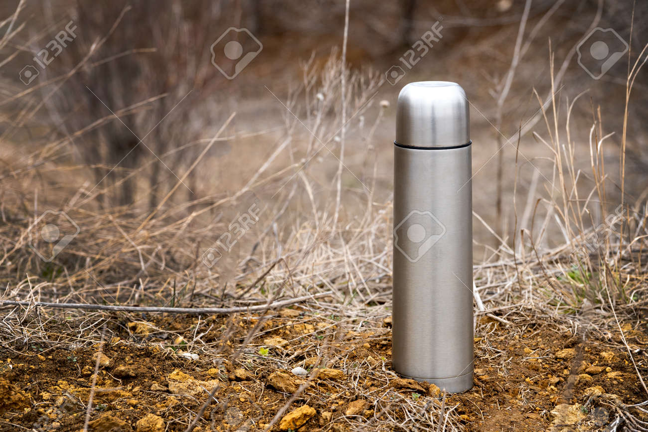 Steel vacuum flask with tea or coffee, outdoor. Hiking, active tourism, picnic, hot drink concept - 165799720