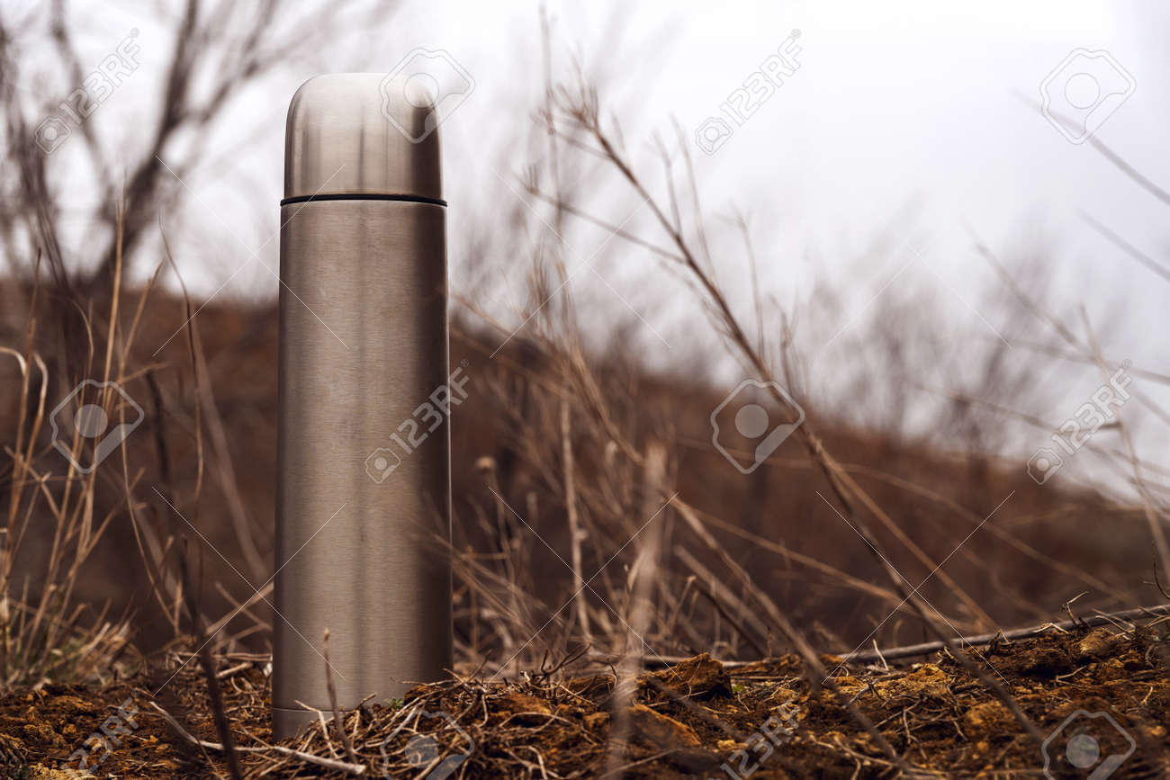 Steel vacuum flask with tea or coffee, outdoor. Hiking, active tourism, picnic, hot drink concept - 165799719