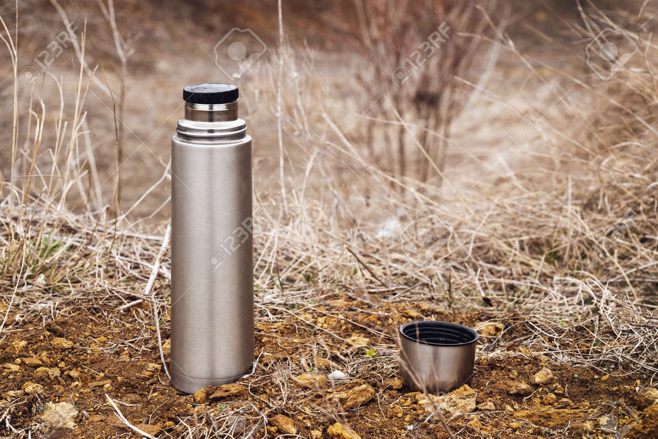 Steel vacuum flask with tea or coffee, outdoor. Hiking, active tourism, picnic, hot drink concept - 165799721