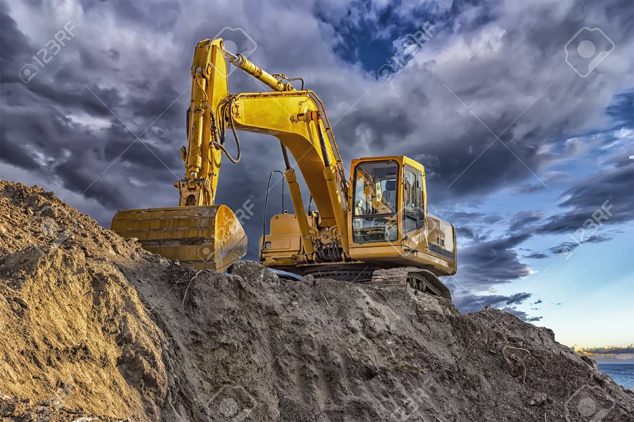 A stopping yellow excavator at an incredibly beautiful sunset - 92680591