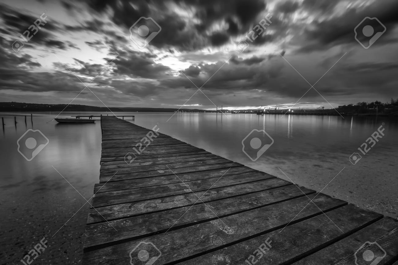 Black and white landscape with wooden pier and fishing boat at