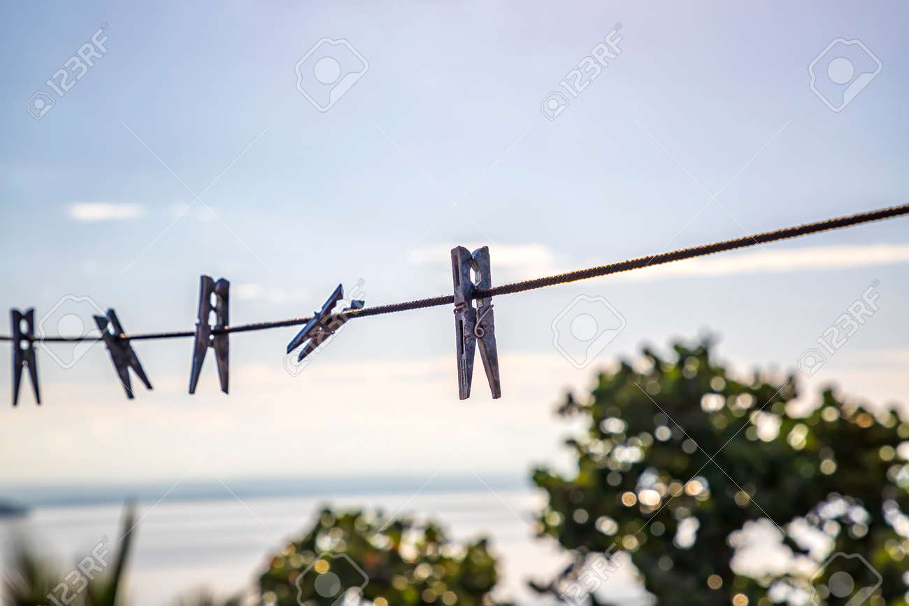 Clothespins holding clothes in laundry. clothespin on a string in a balcony. Abstract view - 164405717