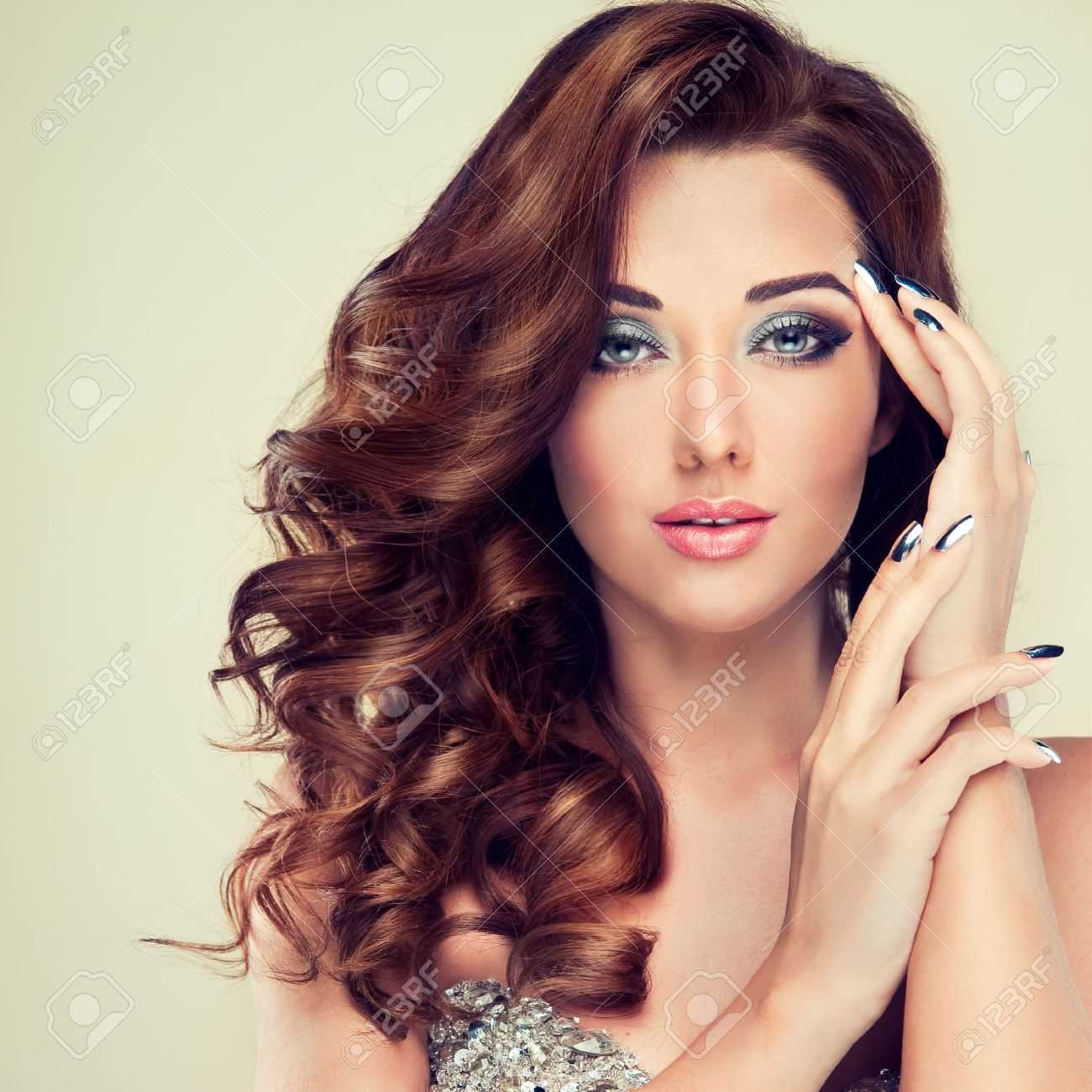 Beautiful model with long curly hair fashion makeup and silver nails Stock Photo - 40147711