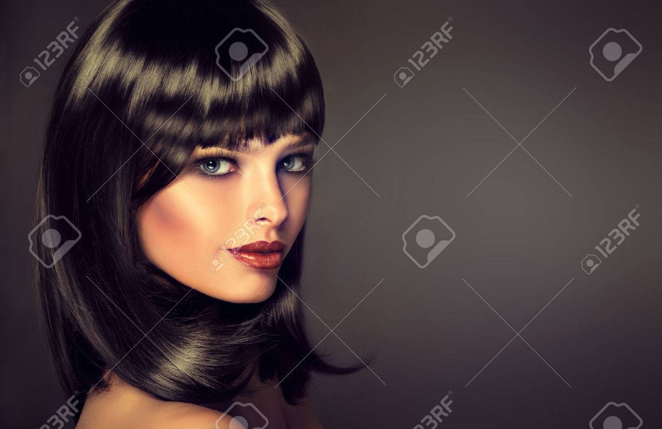 The girl in profile with black straight shiny hair and bangs . Model brunette with hairstyle of the care. Luxury fashion style, hair, cosmetics ,make-up - 47684376