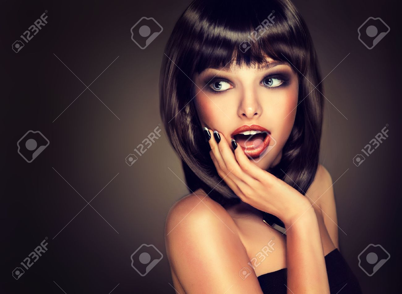Surprised beautiful girl look away . Model brunette with hairstyle of the care. Black hair and a black manicure on the nails.Luxury fashion style, nails manicure, cosmetics ,make-up - 47684128