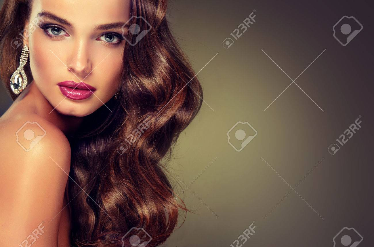 Beautiful model brunette with long curled hair. Luxury fashion style, nails manicure, cosmetics, make-up - 49581641