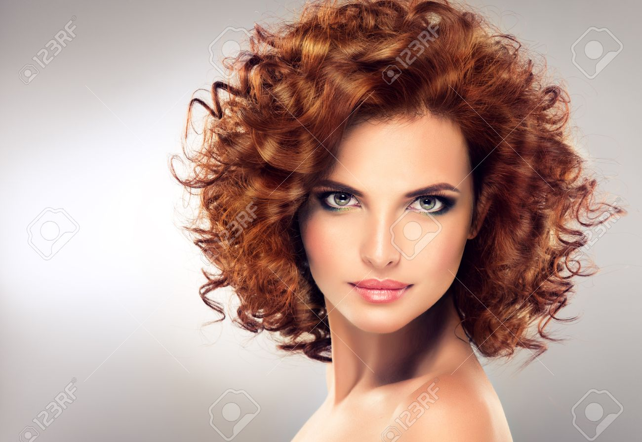 Pretty red haired girl with curls , fashionable makeup. Straight look on camera. - 52034935