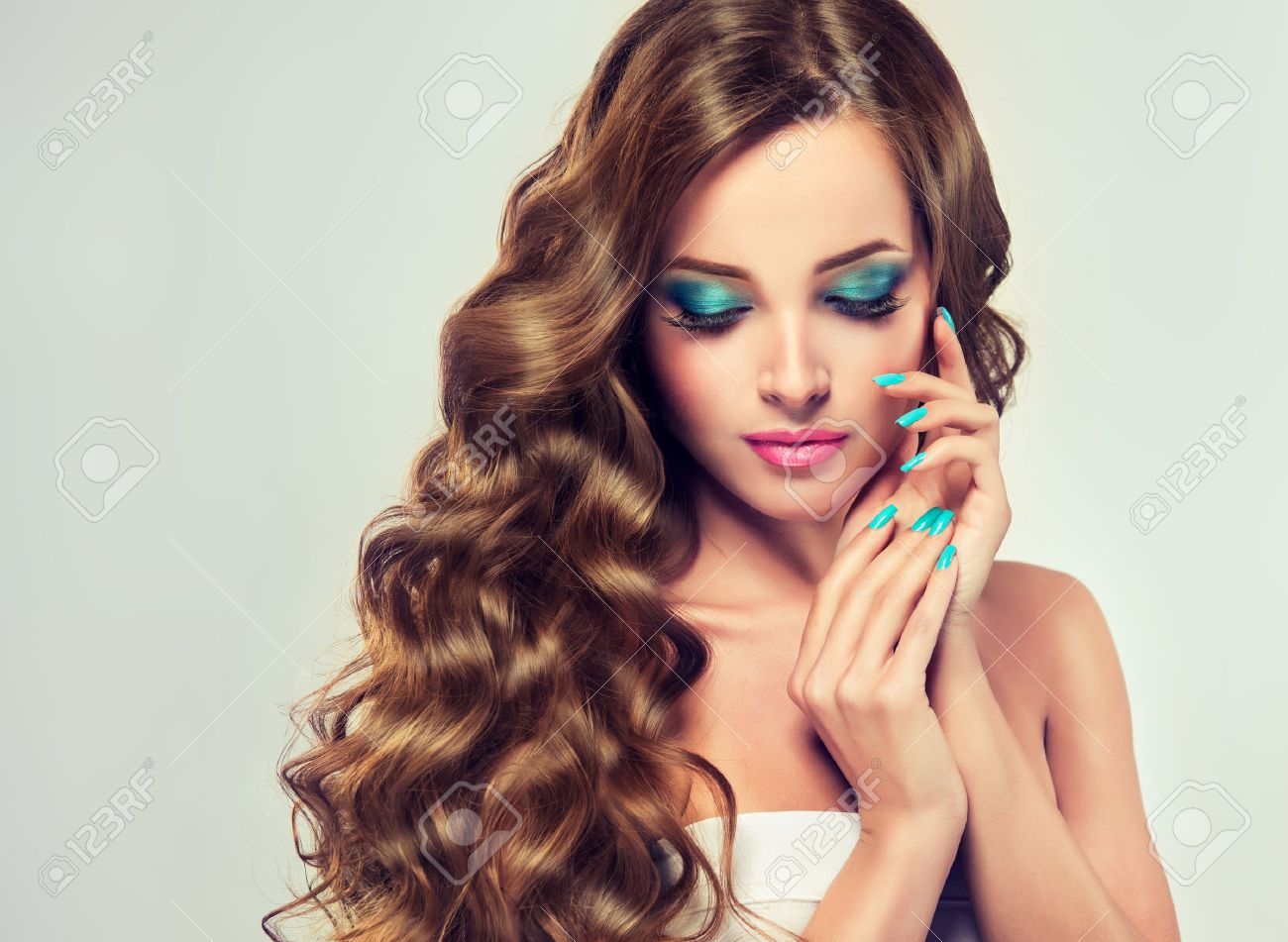 Beautiful model brunette with long and lush curled hair. Luxury fashion style, nails manicure, cosmetics and make-up. - 55393503