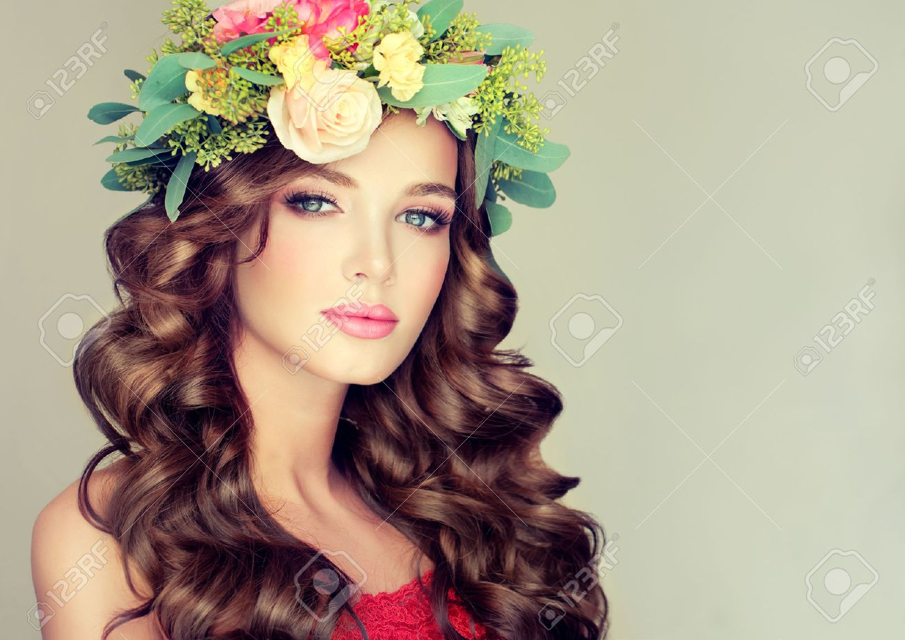 Beautiful woman model brunette with long curly hair floral wreath on the head . Spring girl. - 56453265