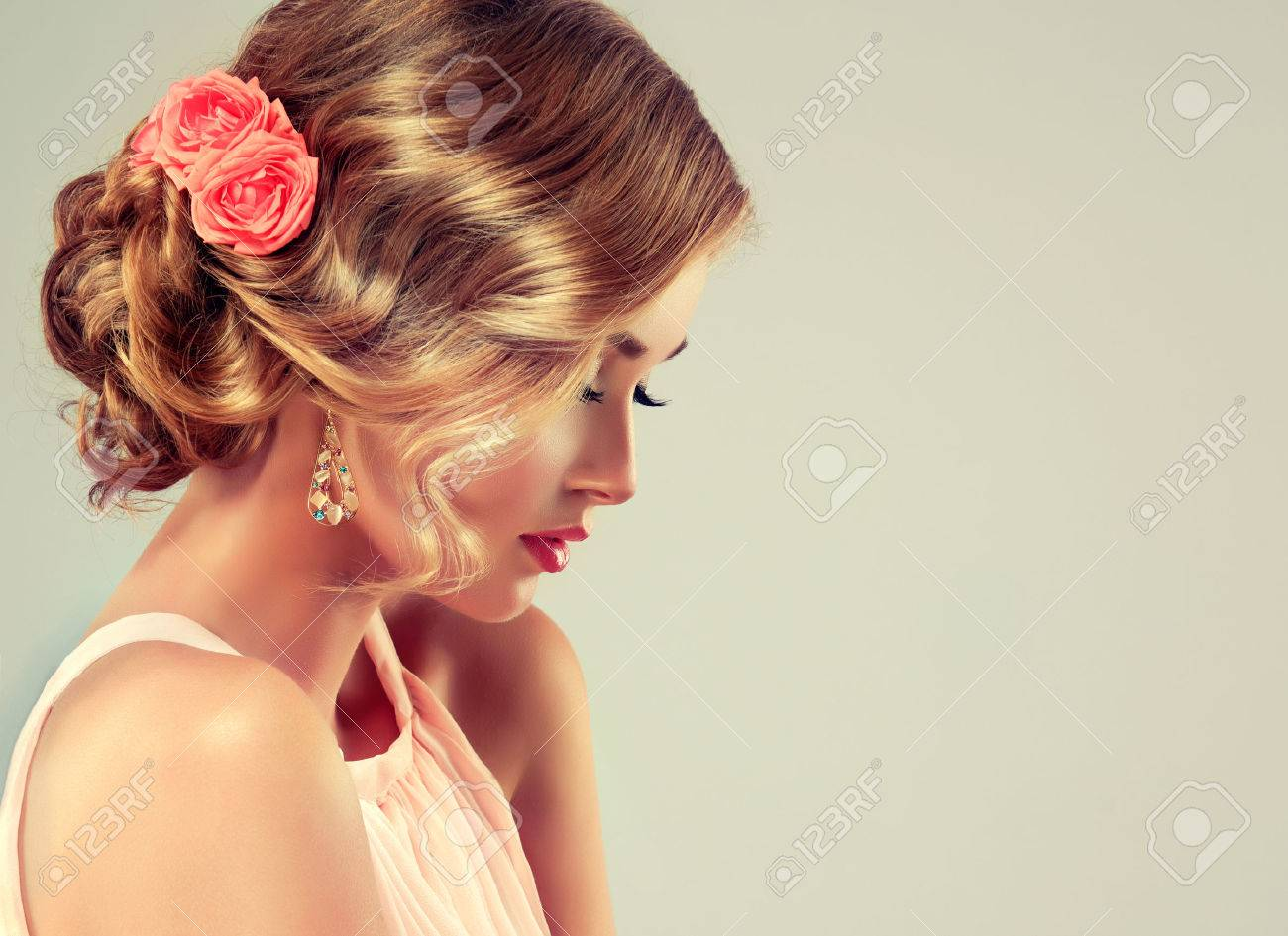 Beautiful model with elegant hairstyle . Beautiful woman with colourful makeup and fashion wedding hairstyle. Rose flowers in the hair. - 57053113