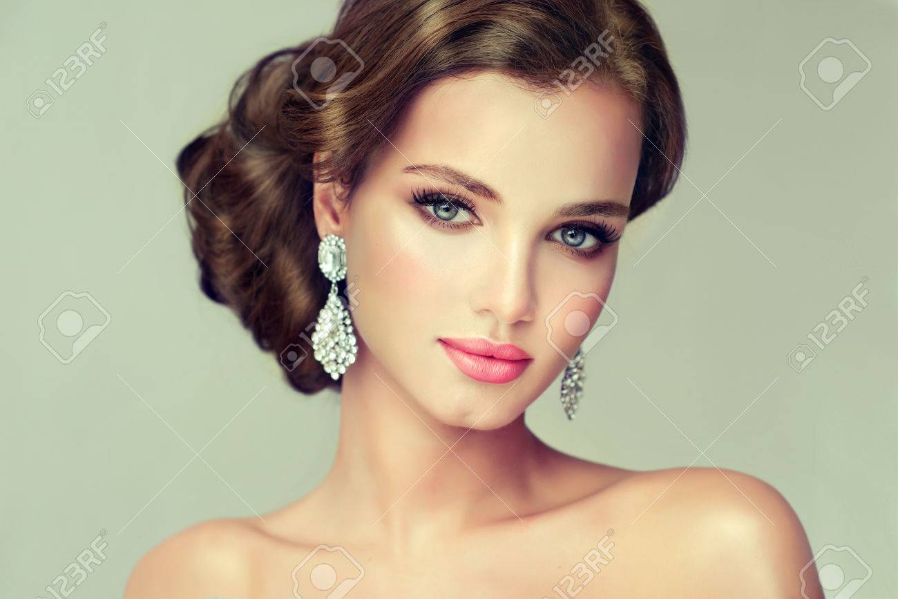 Young, gorgeous model putting on in a delicate make up, and dressed in a red gown. Misty, romantic look. Wedding and evening style. - 57211526