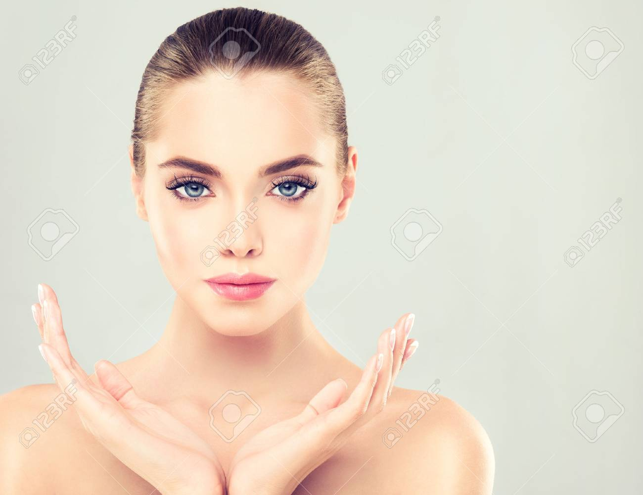 Close-up portrait of young woman with clean fresh skin. Make-up and manicure. - 58233019