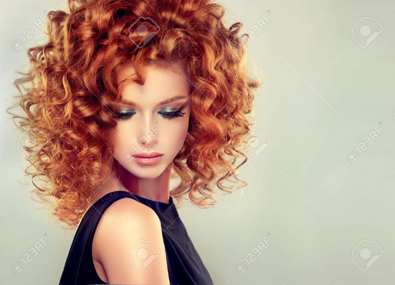 jolie rouge fille aux cheveux bouclés et avec coiffure maquillage élégant  up. portrait gros plan.