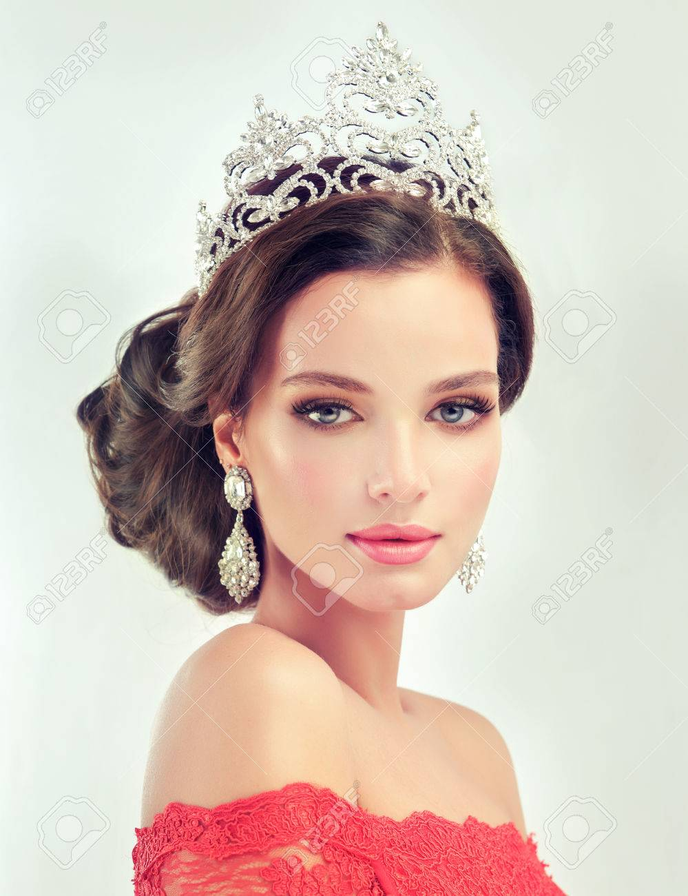 Young, gorgeous model in a delicate make up, dressed in a red gown and crown on her head. Misty, romantic look. Wedding and evening style. - 60303270