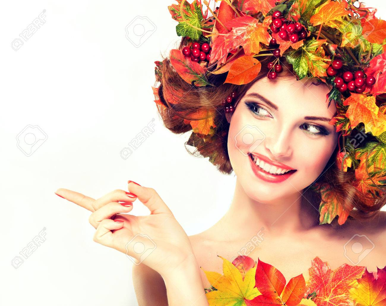 Autumn Beauty. Red and yellow autumn leaves and red berry in wreath on girl head. - 62522721