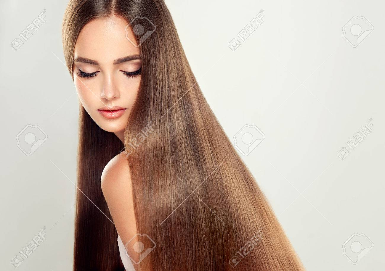 Young attractive girl model with gorgeous, shiny, long, straight brown hair. Good and healthy hair as resalt of right care. - 64010254