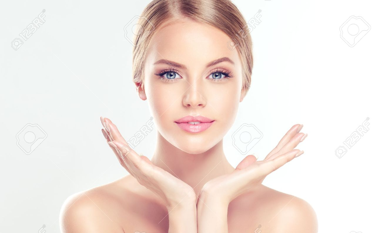 Portrait of beautiful Young, smiling Woman with clean, fresh, skin touching own face. Facial treatment. Cosmetology, beauty and spa. - 70488814