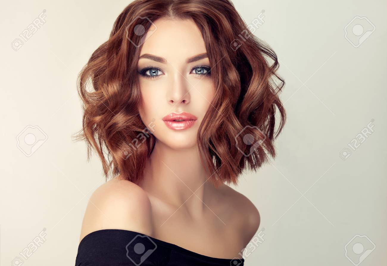 Attractive brown haired woman with modern, trendy and elegant hairstyle. Example of middle length,dense and curly hair.Gentle make up and long eyelashes. - 89144166