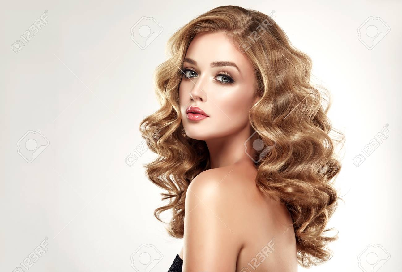 Woman Blonde With Voluminous Shinycurly And Loose Hairstyle