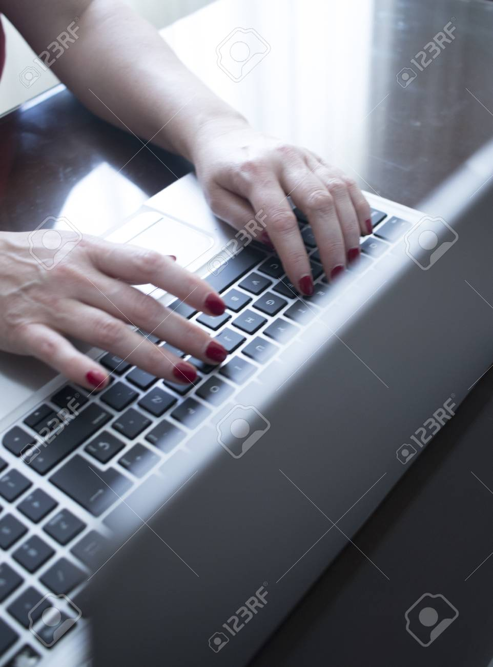 Secretary typist typing on laptop pc computer keyboard keys with hands with  red nail varnish.