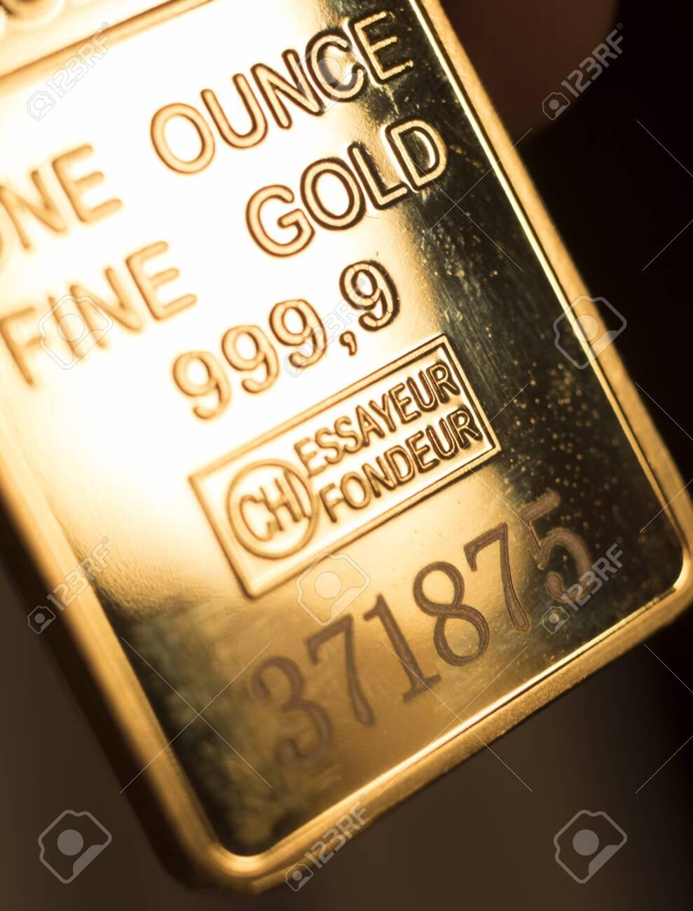 Fine solid gold 999.9 one ounce bullion ingot precious metals bar closeup isolated photo. - 125065924