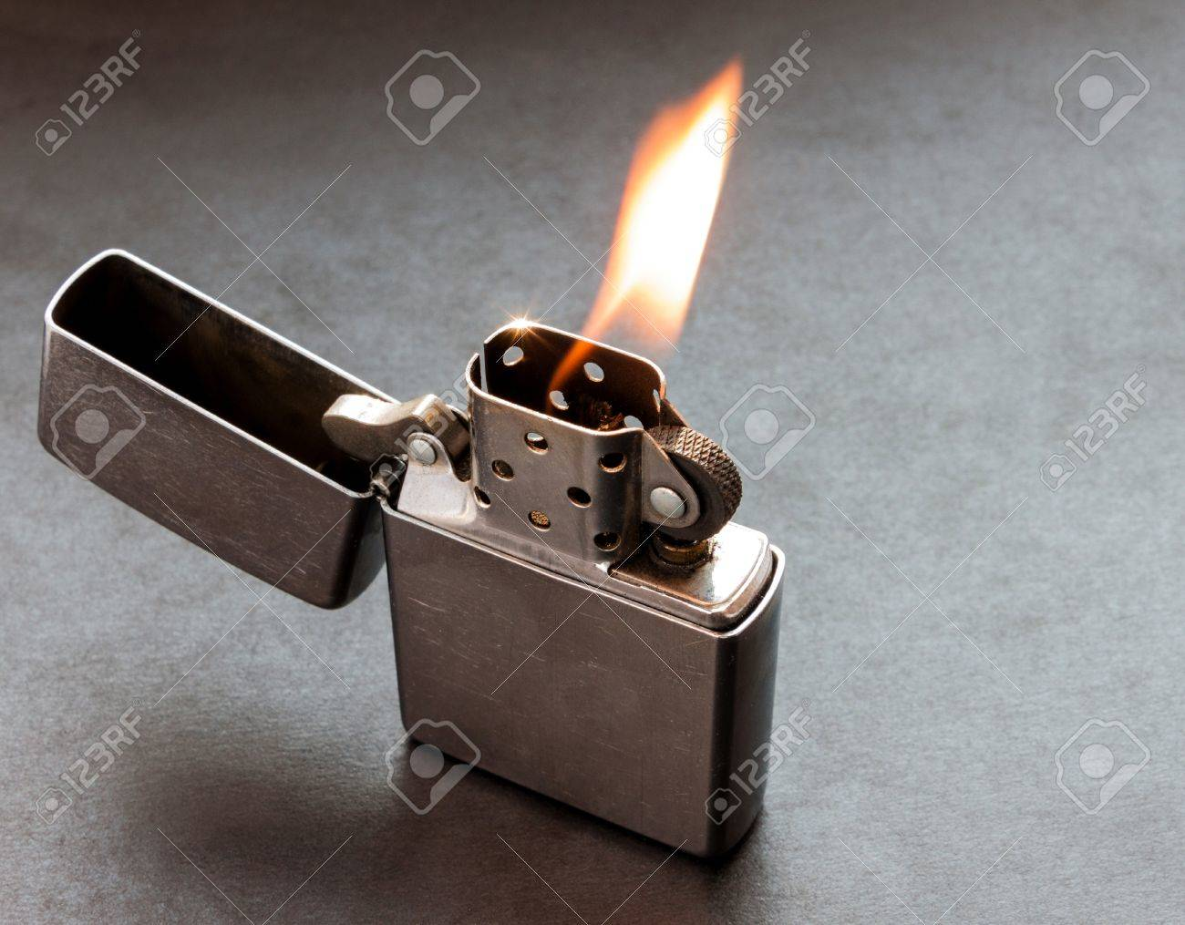 Silver metal lighter on dark background with flame. Stock Photo - 18385730
