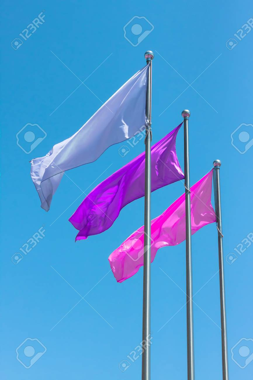 Blue, Purple and pink flags against blue sky