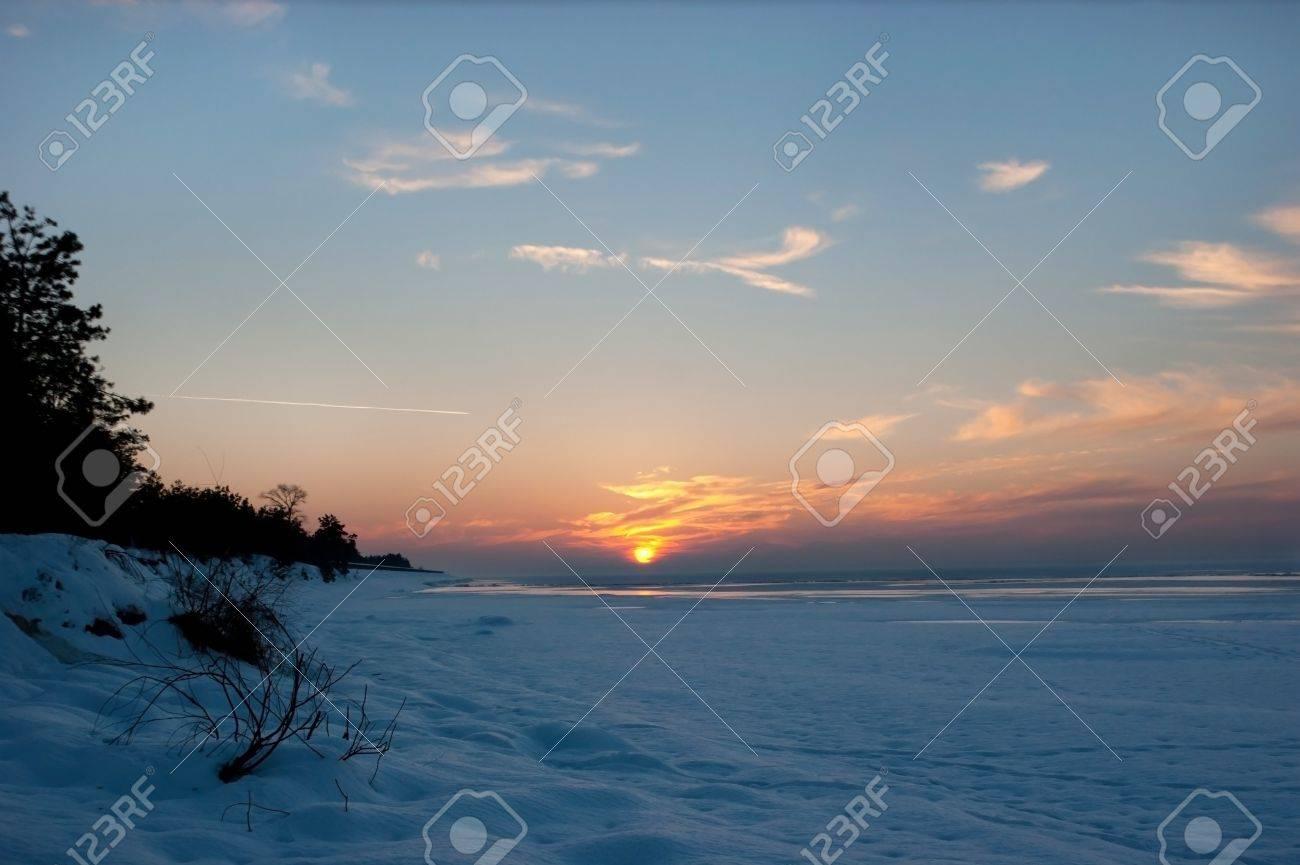 beautiful winter sunset on the kyiv sea, ukraine the clouds around the sun look like fire Stock Photo - 19198090