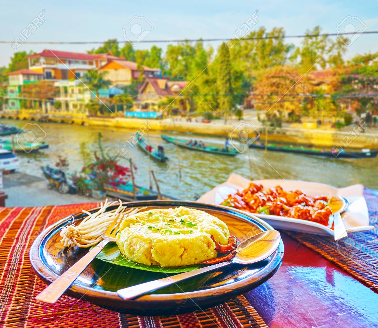 Enjoy traditional Burmese cuisine with a view on Inle Lake canal - banana leaf wrap with sticky rice and vegetables in outdoor terrace of cafe in Nyaungshwe, Myanmar. - 121649034