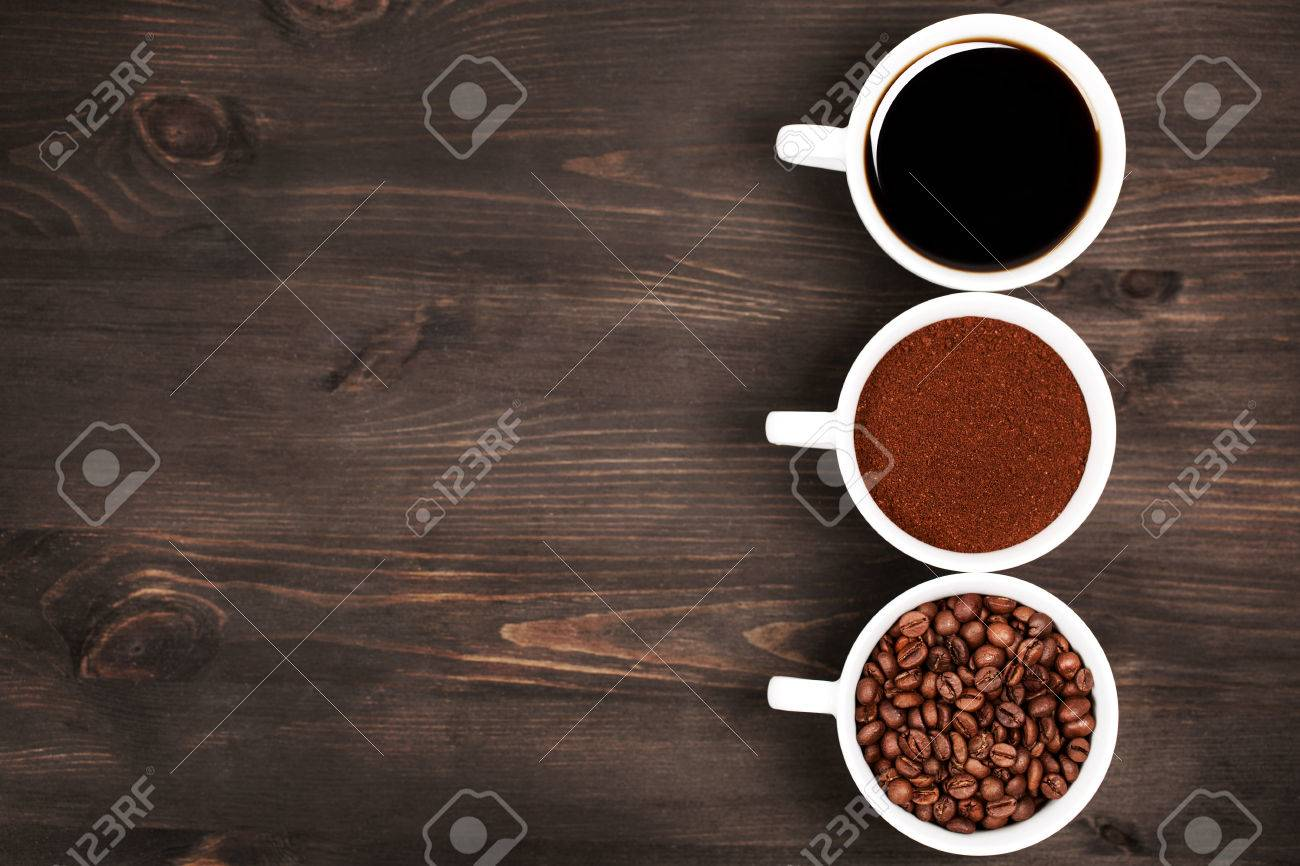 Three cups with different states or stages, or conditions, or black coffee. Dark wooden background. - 51074474