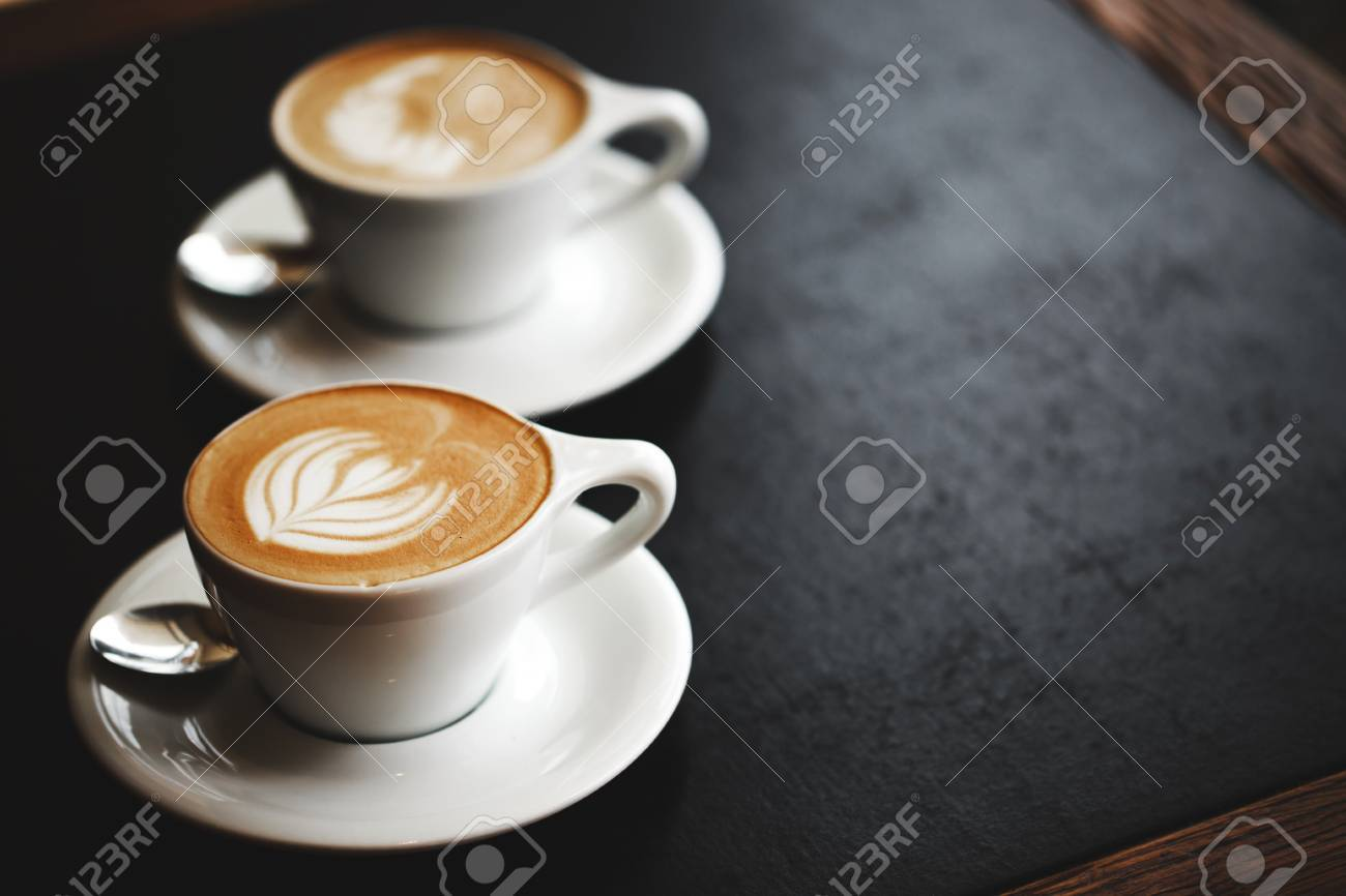Stock Photo   Two Cups Of Cappuccino With Latte Art On Black Table. Morning  Coffee For Couple In Love. Top View.