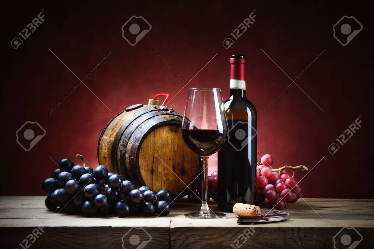 Red wine glass with bunches of grapes, bottle and small barrel on old wooden table. - 142650259