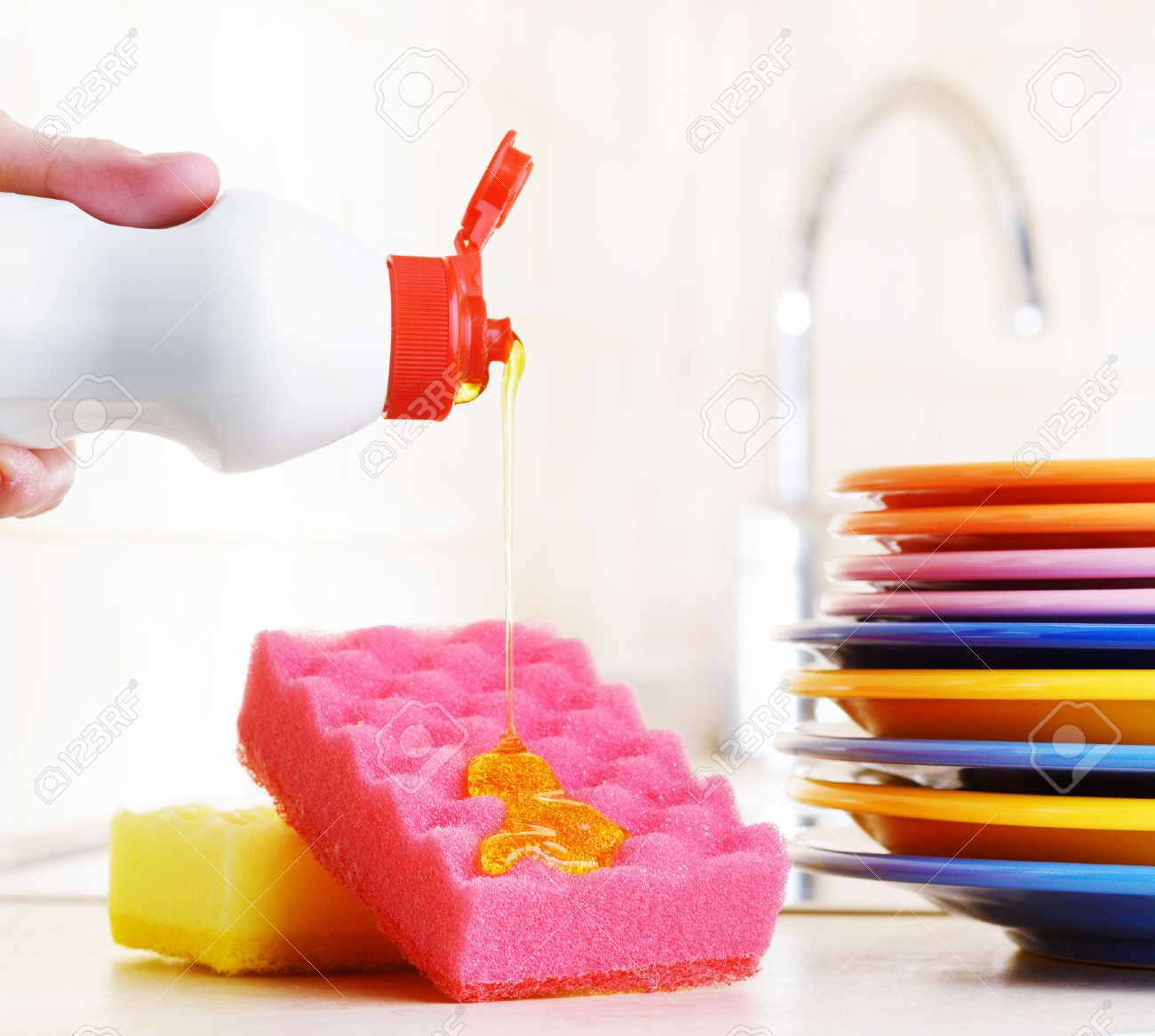 Several Colorful Plates, A Kitchen Sponges And A Plastic Bottle ...