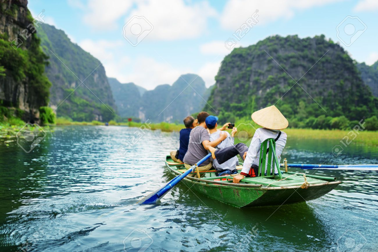 Tourists traveling in boat along the Ngo Dong River and taking picture of the Tam Coc, Ninh Binh, Vietnam. Rower using her feet to propel oars. Landscape formed by karst towers and rice fields. - 51646804
