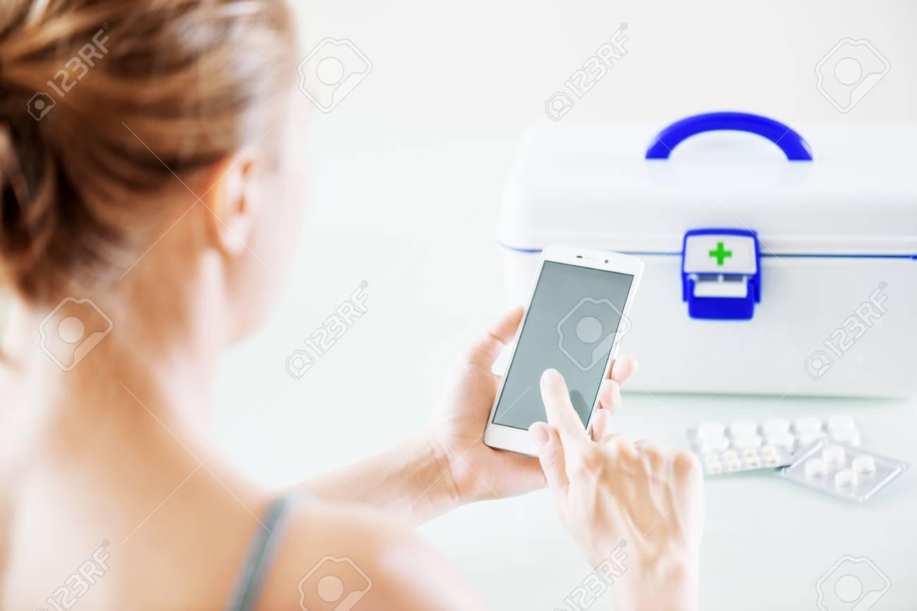 1a9e708e264 Stockfoto - Vrouw die smartphone voor het kopen van drugs in online  apotheek gebruiken en thuis medisch overleg krijgen. Witte doos met  EHBO-kit en pillen ...