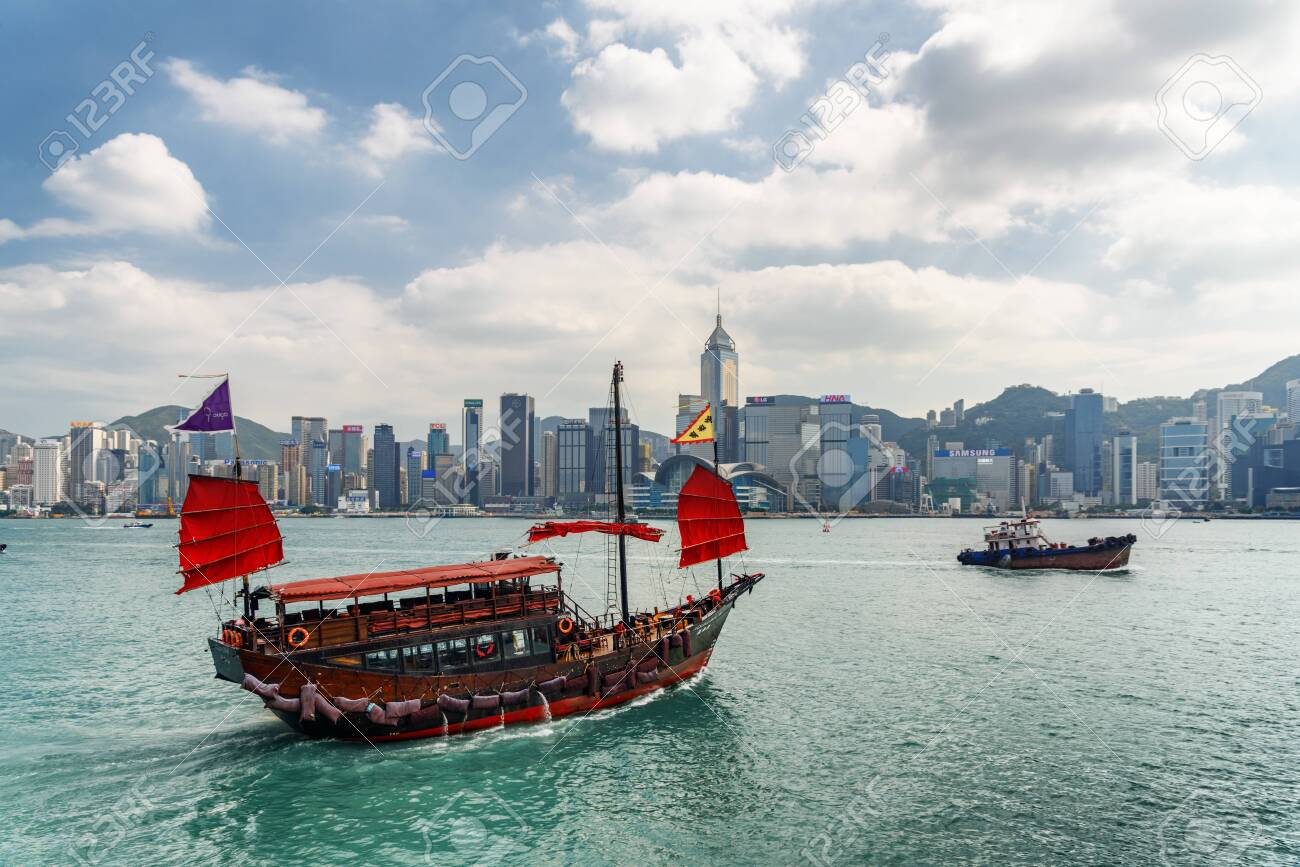 Hong Kong - October 20, 2017: Awesome view of traditional Chinese wooden sailing ship with red sails in Victoria harbor. Hong Kong Island skyline on sunny day. Amazing cityscape. - 147379259