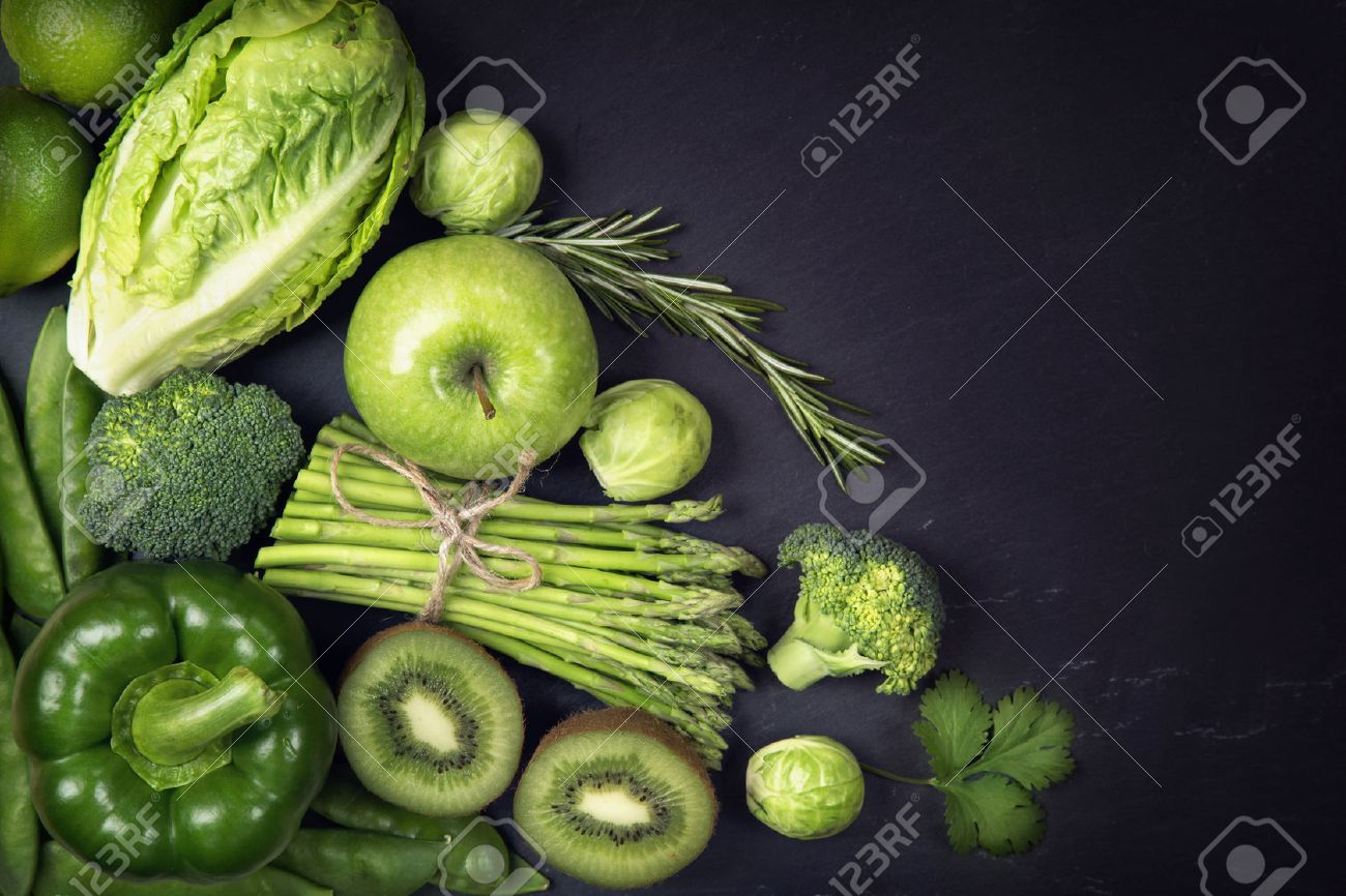 Green healphy vegetables and fruits on a black slates - 54145215