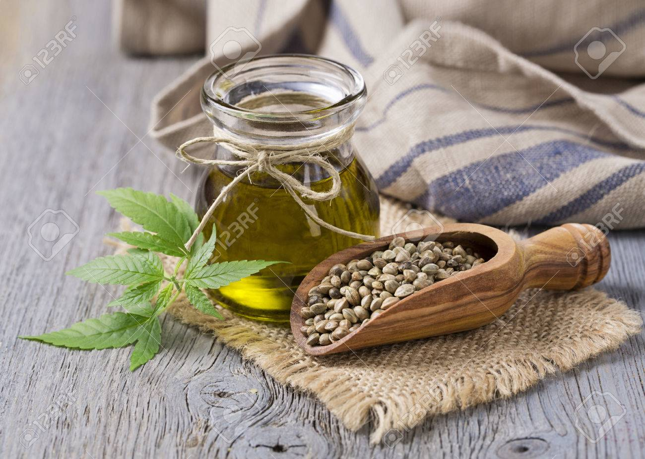 Hemp oil n a glass jar and hemp seeds - 55678040