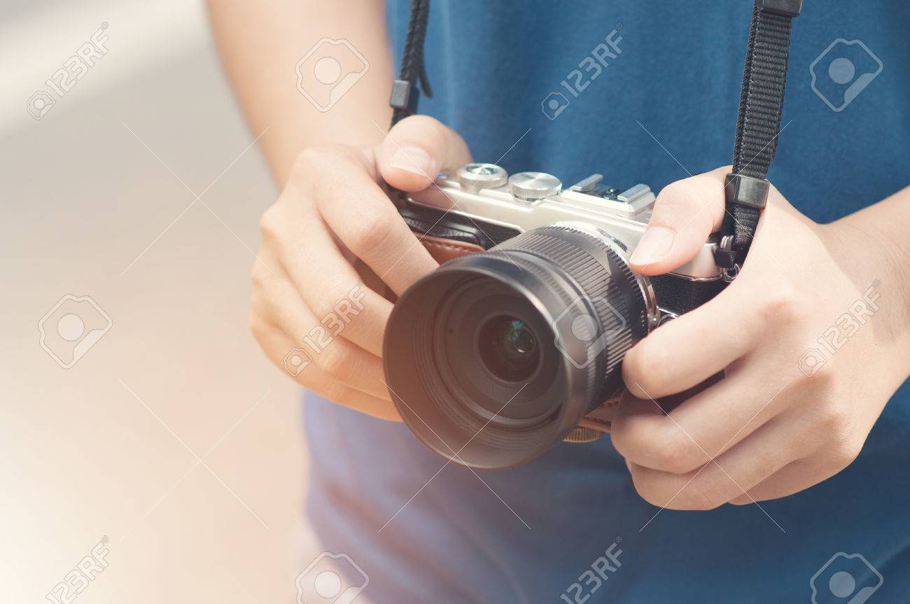 Stock Photo   Woman Hands Holding Vintage Mirrorless Camera.