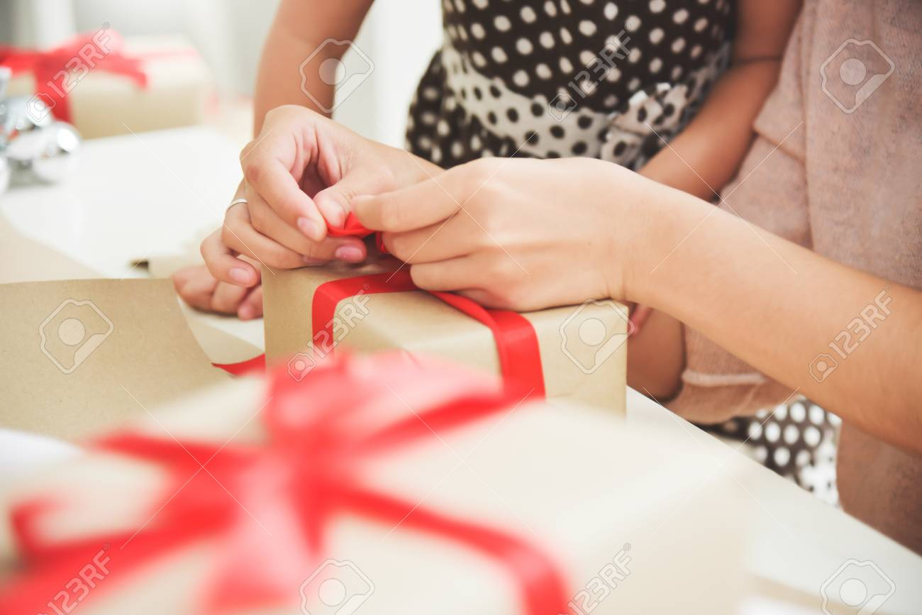 Closeup Young Mother And Her Daughter Hands Wrapping A Brown Gift Box For Birthday Christmas