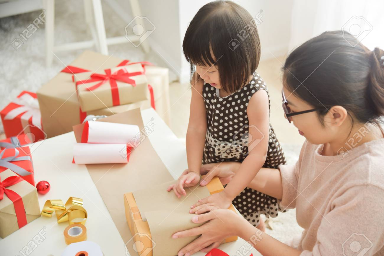 Young Mother And Her Daughter Wrapping A Gift Box For Birthday